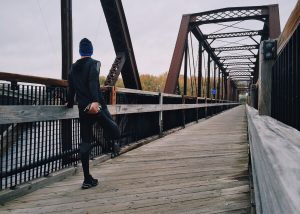 Man Stretching on Bridge